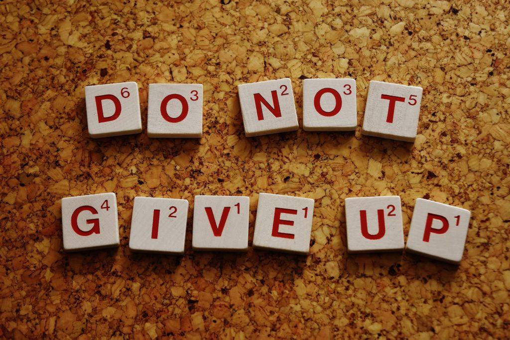 Auf diesem bild liegen Scrabble Steine in zwei Reihen, Auf ihnen steht auf englisch Do not give up.